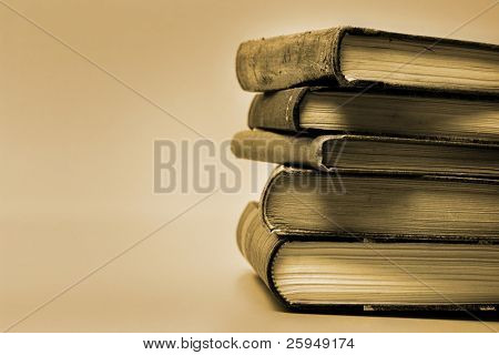 Sepia toned image of stacked books.