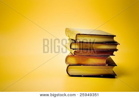 Stacked books against a yellow background.