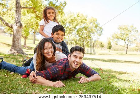 Young kids and parents lying in a pile on the grass in park
