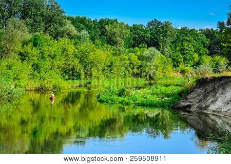 Solitude On The River - A Fisherman On A Boat. Evening Peace And Quiet Of The River, A Fisherman On