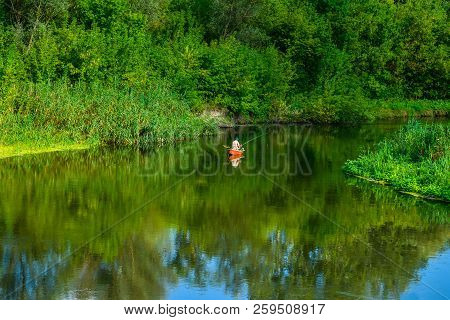 Solitude On The River - A Fisherman On A Boat. Summer Calm Evening, A River And A Lone Fisherman On