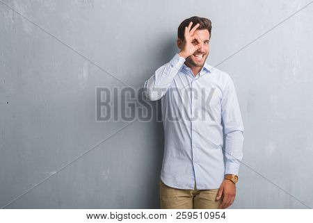 Handsome young business man over grey grunge wall wearing elegant shirt doing ok gesture with hand smiling, eye looking through fingers with happy face.