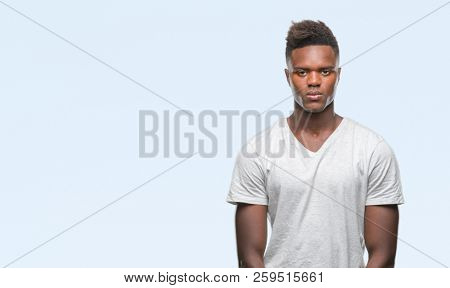 Young african american man over isolated background with serious expression on face. Simple and natural looking at the camera.