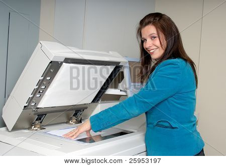 Young Woman At Work In The Photocopier Room At Her Office