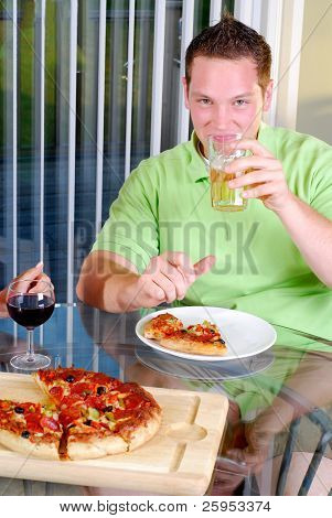 Handsome Young Man Drinking Beer With His Pizza Meal At Home