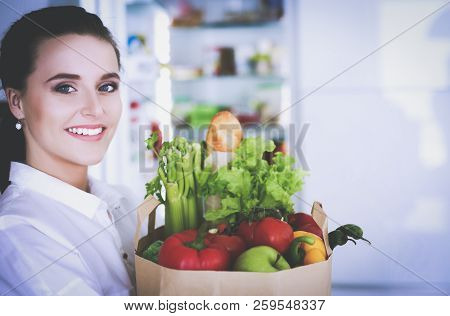 Young Woman Holding Grocery Shopping Bag With Vegetables .standing In The Kitchen. Woman In The Kitc