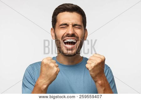 Closeup Of Emotional Man Isolated On Gray Background, Screaming With Joy And Victorious Expression,