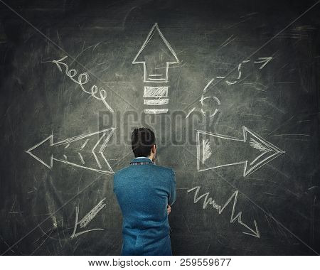 Rear View Of Pensive Businessman Thinking In Front Of A Huge Blackboard With Arrows Pointed To Diffe