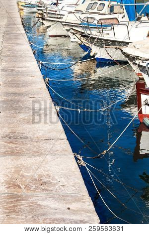 Small Fishing Boats In The Harbor. Detail On The Bow Of The Boat. Tied Boats In The Harbor. Port On