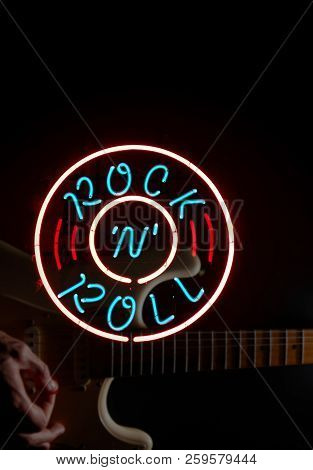Musician Playing Electric Guitar With Neon Rock N Roll Sign -- Sign Is Sharp