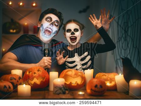 Father and his kid having fun at home. Happy family celebrating Halloween. People wearing carnival costumes and makeup.