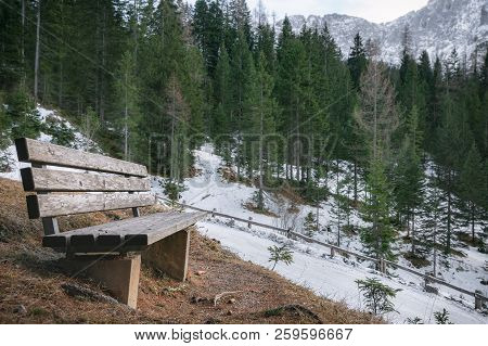 Early Winter Landscape With A Wooden Bench On The Side Of An Alpine Road, Snowy Fir Forest And Mount