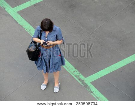 Brunette Girl Standing With A Smartphone On The Street, View From The Top. Concept For Text Messagin