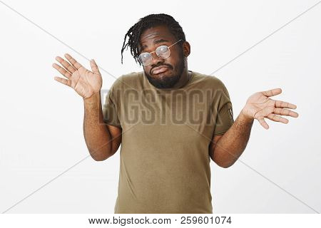 He Knows Nothing. Portrait Of Unaware Clueless Cute African-american Brother In Olive T-shirt And Gl