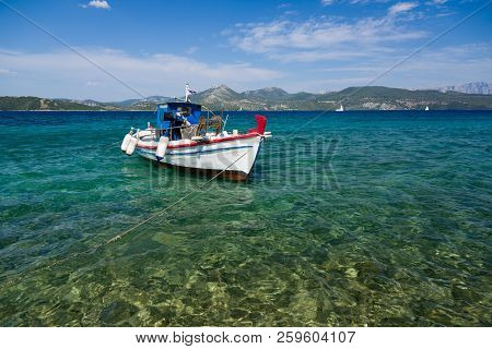 White Fisher Boat Floats On Crystal Clear Water In Greece