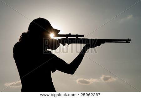 Young man shooting with a rifle, against sunset with a sunburst between the scope and his eye
