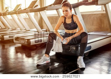 Beautiful Asian Young Woman Tired Taking A Break From Running Or Exercise Sitting On Treadmill Machi