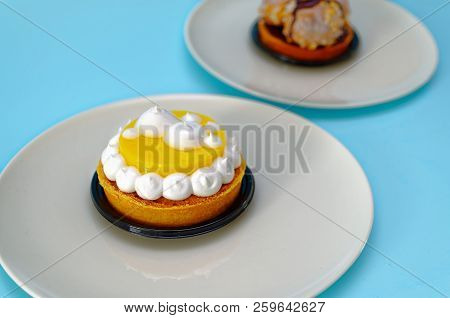 Two Cake Particles With Lemon And Chocolate On Two White Plates By A Pastry Chef With Light Blue Bac