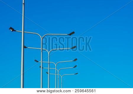 A Line Of Lightposts Against A Bright Blue Sky.