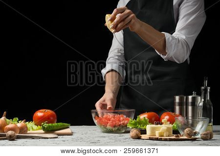 The Chef Prepares A Salad, Pours Lemon Juice On A Dark Background With An Empty Space For Writing