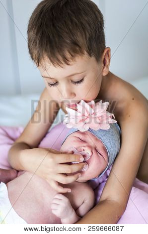 Cute Caucasian Pre-school Age 6 Year Old Child Comforting His Newborn Baby Sister Crying. He Gives H