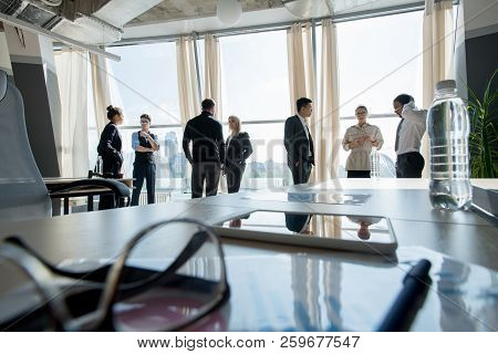 Workplace With Business Objects And Touchpad With Business Group Cooperating During Break