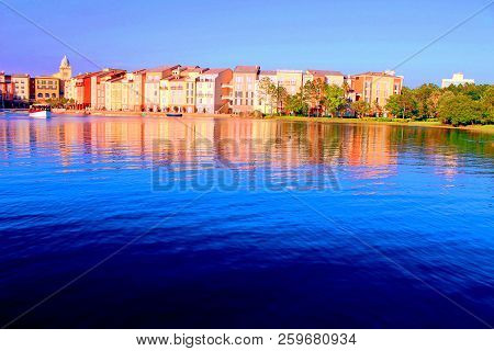 Italian city replica in Orlando, USA: the blue water bathes the shores of a pleasant-seaview town, reflecting an amalgam of vivid painted colors of buildings, fishing boats and green trees. Scenic view. poster