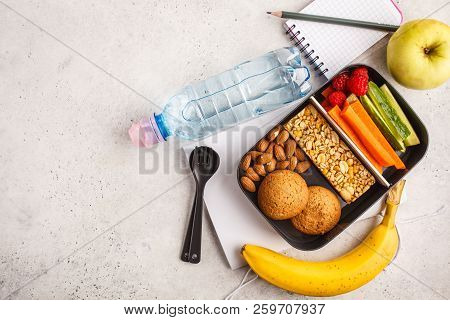 Healthy Meal Prep Containers With Cereal Bar, Fruits, Vegetables And Snacks. Takeaway Food On White