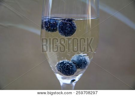 Bubble Coated Blueberries Floating In A Glass Of Champagne