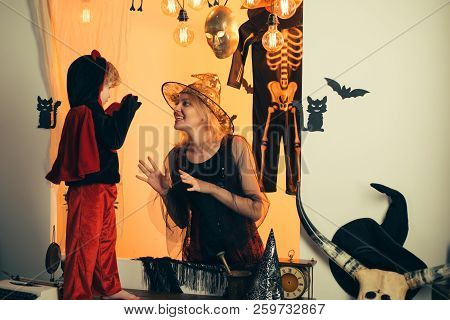 Halloween Dresses On Mother And Son And Witch Costumes And Witch Hats. Background Decorated For Hall