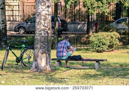 Szeged, Hungary, August 30: Young Man - Cyclist Resting Sitting On A Bench And Talking On A Mobile P
