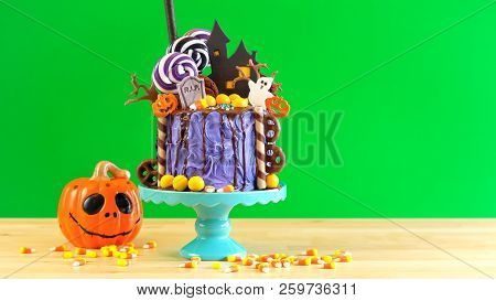 On Trend Halloween Candyland Novelty Drip Cake Against Green Background.