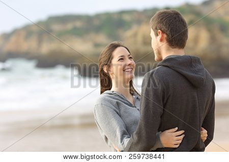 Happy Couple Of Teens Hugging And Looking Each Other On The Beach