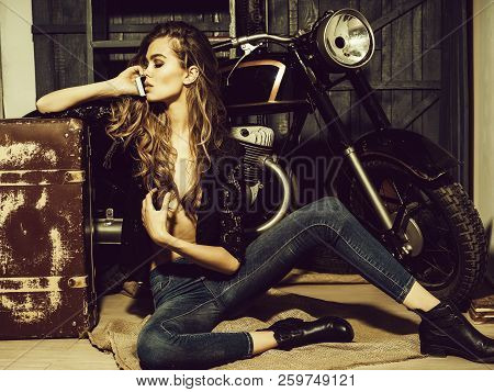 Girl Biker Or Pretty Woman With Long, Blond Hair In Erotic Shirt And Jeans With Vintage Suitcase At