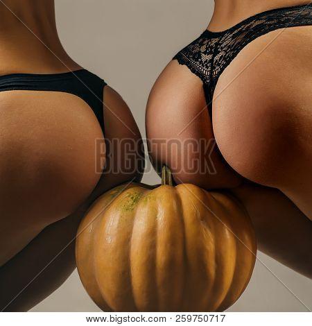 Buttocks ass and pumpkin close-up. Pumpkin ass. Sexy Halloween art design. Pumpkins isolated on girl with big bum. Trick or treat. Pumpkin head jack lantern. Carved Pumpkin - funny concept poster