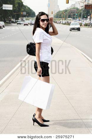 La niña va en la calle con un bolso de compras
