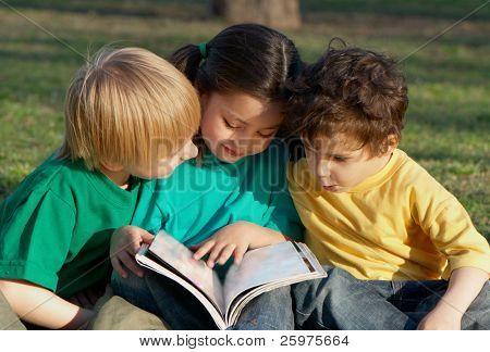 Grupo de crianças com o livro em uma grama no Parque