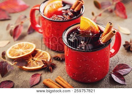 Two Cups Of Autumn Mulled Wine Or Gluhwein With Spices And Orange Slices On Rustic Table Top View. T