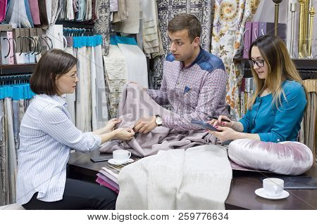 Young Couple Of Small Business Owners Of Fabric Store Talk And Advise The Buyer.