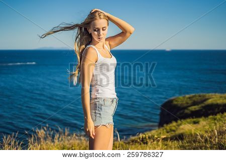 Young Woman In Jeans Shorts Posing Against The Blue Sea. Wearing Jeans Stylish Shorts And Striped Sh