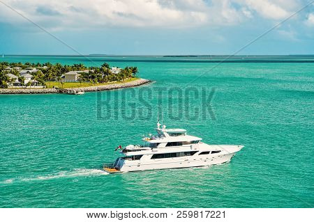 Cruise Touristic Boat Or Yacht Floating Near Island With Houses And Green Trees On Turquoise Water A