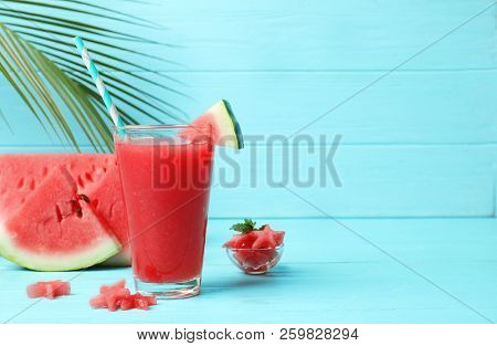 Summer Watermelon Drink In Glass And Sliced Fruit On Table Against Color Background With Space For T