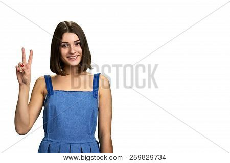 Portrait Of Smiling Girl Showing Peace Gesture. Pretty Caucasian Woman Gesturing Victory, Isolated O