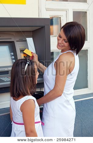 Happy family withdrawing money from credit card at ATM