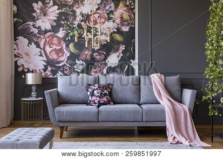Real Photo Of A Living Room Interior With A Sofa, Pillow, Blanket And Flowers On Wallpaper