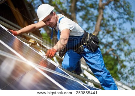 Professional Technician Installing Solar Photo Voltaic Panel Standing On High Metal Platform On Blue