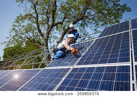 Two workers on tall steel platform installing heavy solar photo voltaic panel using screwdriver on green tree and blue sky background. Solar panel system installation, professionalism concept. poster