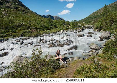 Hiker Sitting Near Mountain River On Besseggen Ridge In Jotunheimen National Park, Norway