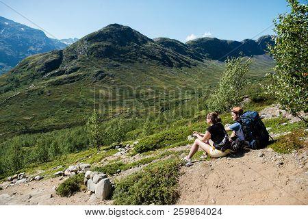 Couple Of Hikers Resting On Besseggen Ridge In Jotunheimen National Park, Norway