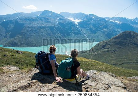 Couple Of Hikers Resting And Looking At Besseggen Ridge Over Gjende Lake In Jotunheimen National Par